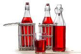 Beyaz eski masada kırmızı suyuyla vintage şişeler — Stok fotoğraf