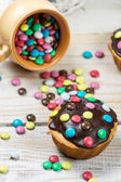 Easter muffins with candies and chocolate glaze — Stock Photo