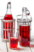 Closeup of red juice in vintage bottles on white background — Stock Photo