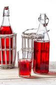 бутылки в корзине с красный сок на белом фоне — Стоковое фото