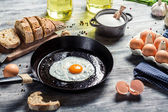 Closeup of frying eggs and fresh bread — Stock Photo
