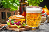 Closeup of fresh burger and a cold beer — Stock Photo
