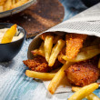 Closeup of Fish & Chips served in the newspaper - Stock Photo