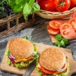 Two burgers and fresh vegetables - Stock Photo