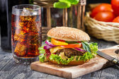 Closeup of homemade hamburger and a Coke with ice — Stock Photo