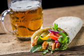 Kebab served with cold beer on old wooden table — Stock Photo