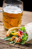 Tasty kebabs and cold beer on old wooden table — Stock Photo