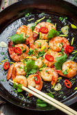Shrimps and chopstick on pan with fresh herbs — Stock Photo