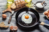Fried egg on a pan served with homemade bread — Stock Photo