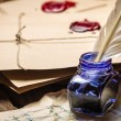 Ancient scrolls and old envelope with blue inkwell - Stock Photo