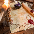 Closeup of table filled with old messages and candles - Stock Photo