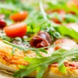 Closeup of pizza with parma ham and arugula — Stock Photo