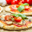 Close-up on freshly baked mini pizzas — Stock Photo #25700787
