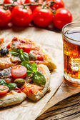 Baked pizza served with a cold drink — Stock Photo