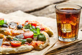 Baked pizza and served with cold drink — Stock Photo