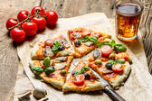 Baked pizza with fresh ingredients on old wooden table — Stock Photo
