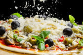 Falling cheese on a freshly prepared pizza on black background — Stock Photo