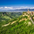 Ancient city on hill in Tuscany on a mountains background. — Stock Photo