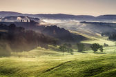 Collines embrumées et prairies en toscane au lever du soleil — Photo