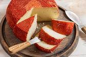 Closeup žluté tvrdý sýr s červenou pečetí — Stock fotografie