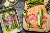 Closeup of asparagus rolled in ham and baked with cheese — Stock Photo