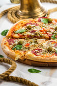 Closeup of Fresh pizza with salami, olives and basil — Stock Photo