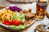 Vegetables, fries and meat kebab on a plate — Stock Photo