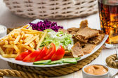 Closeup of vegetables, fries and meat kebab served with cold Cok — Stock Photo