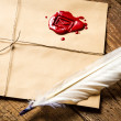 Closeup of feather on envelope with red sealant and inkwell — Stock Photo #27393607
