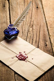 Blue ink inkwell with feather on envelope with red sealant — Stock Photo