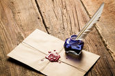 Blue ink inkwell and envelope with red sealant — Stock Photo