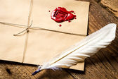 Closeup of feather on envelope with red sealant and inkwell — Stock Photo