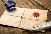 Old feather, envelope, sealing wax and ink bottle — Stock Photo
