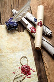 Inkwell and ancient scrolls on wooden table — Stock Photo