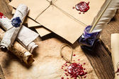 Old scrolls, sealing wax, old envelope and blue ink on wooden ta — Stock Photo