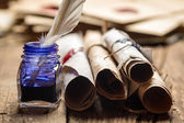 Closeup of old scrolls and blue ink in the inkwell — Stockfoto