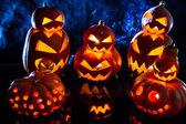 Gruppe seltsame halloween kürbisse auf schwarzem hintergrund mit rauch — Stockfoto