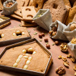 Baked gingerbread cottage elements with the ingredients for deco — Stock Photo