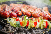 Sausages and skewers on the grill — Stock Photo