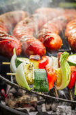 Closeup of sausages and skewers on the grill — Stock Photo
