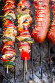 Hot skewers and sausages on the grill — Stock Photo