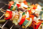 Closeup of skewers with chiken and vegetables on the grill — Stock Photo