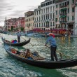 Gondoliers sailing with tourists on the Grand Canal at sunset in — Stock Photo