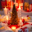 Candlelight, wafer and gifts on the Christmas table — Stockfoto