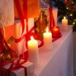 Many gifts near Christmas tree in candlelight — 图库照片 #31646573