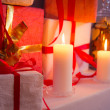 Closeup of gifts near Christmas tree in candlelight — Stock Photo #31646793