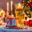 Foto Stock: Candlelight and gifts all around Christmas table