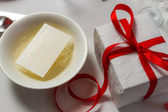 Closeup to wafer and a gift on the Christmas table — Stock Photo