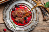 Closeup on venison served with cranberry sauce — Stock Photo