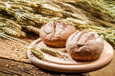 Two buns on the background of grain with ears — Stock Photo